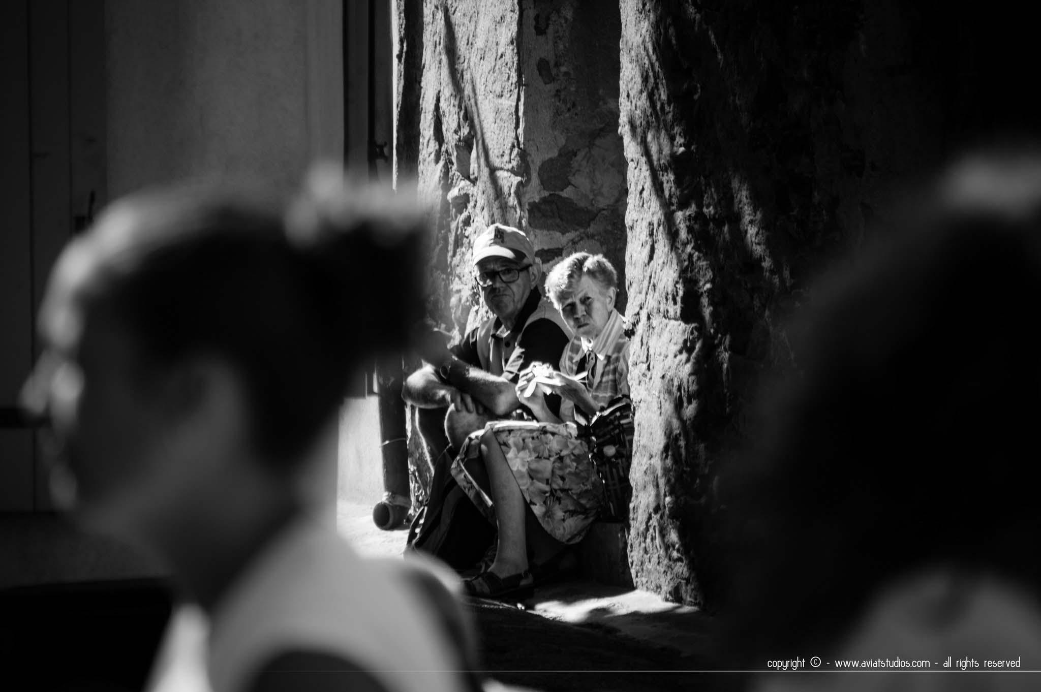 fête de la Châtaigne de Collobrières - un couple de visiteurs âgés assis sur des marches dans une ruelle