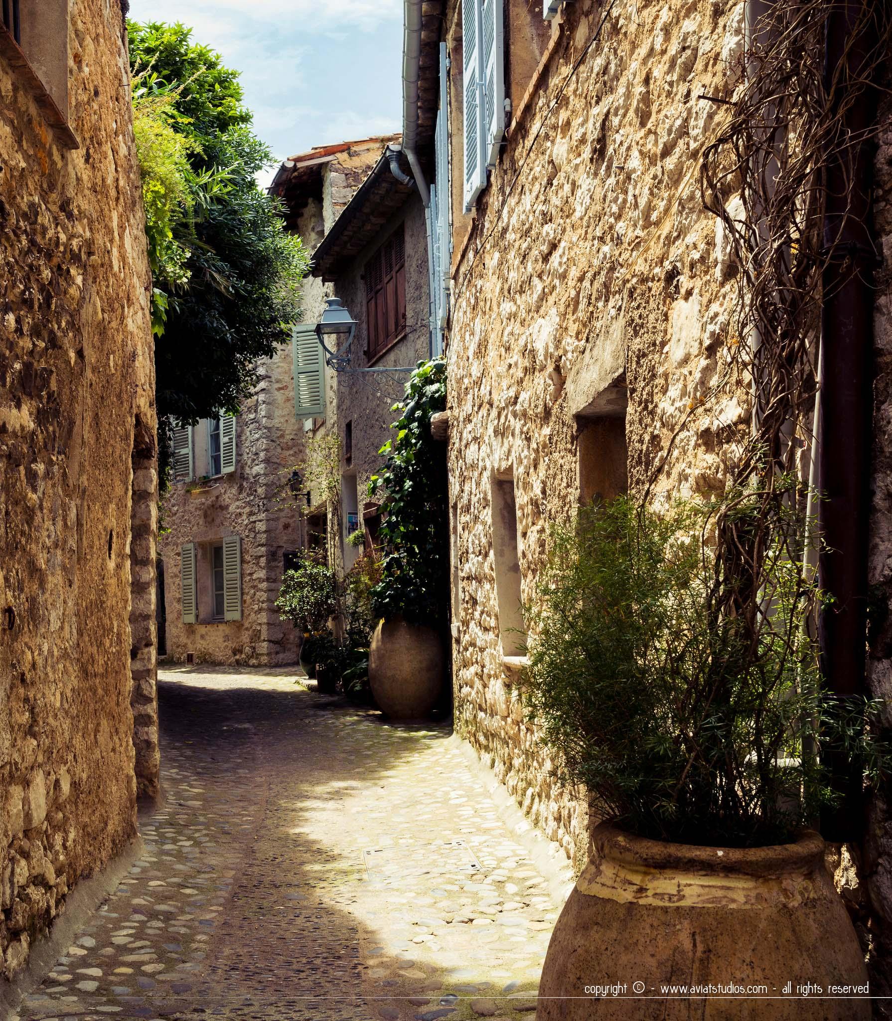 Saint-Paul-de-Vence - une rue déserte avec des murs en pierre jaune et du soleil