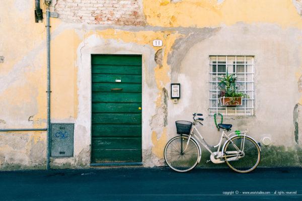 journée à Lucca - une façade un peu décrépie avec une porte verte et un vélo contre la façade