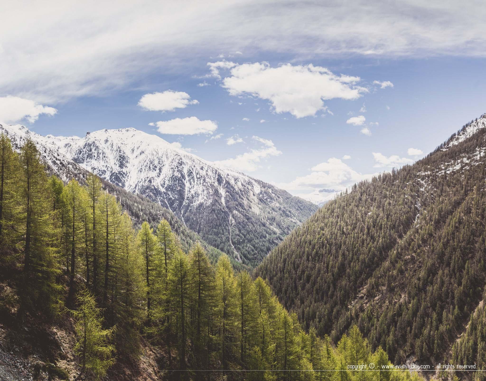 Vallée de la Tinée avec trois montagnes l'une devant l'autre sous un ciel nuageux