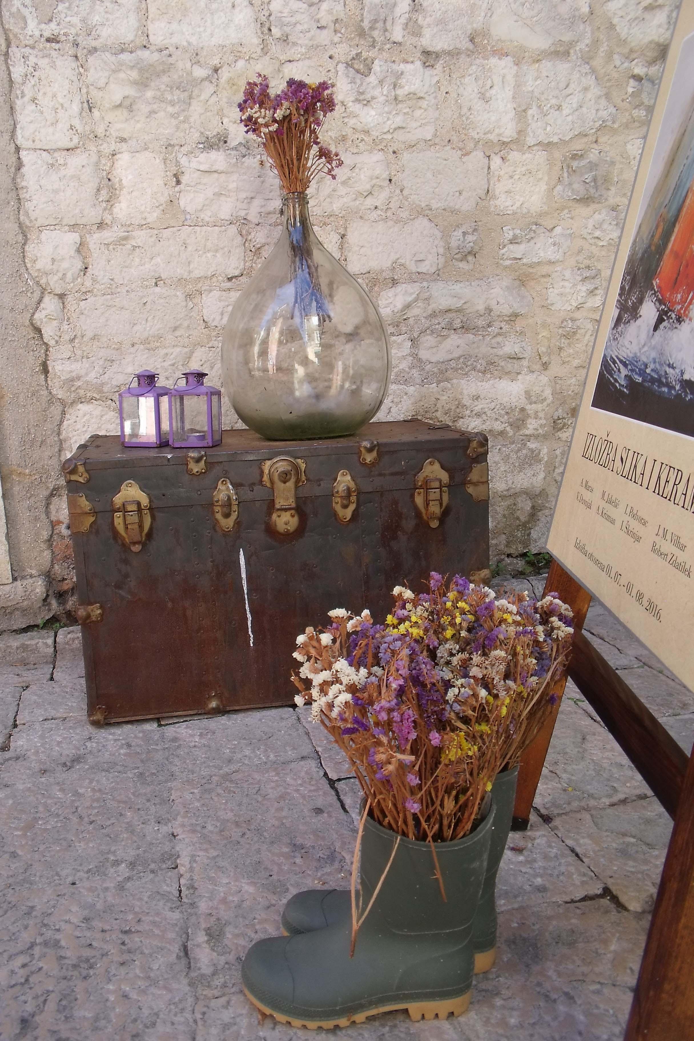Quelques jours à Zadar - un bouquet de fleurs séchées dans une paire de bottes devant une galerie