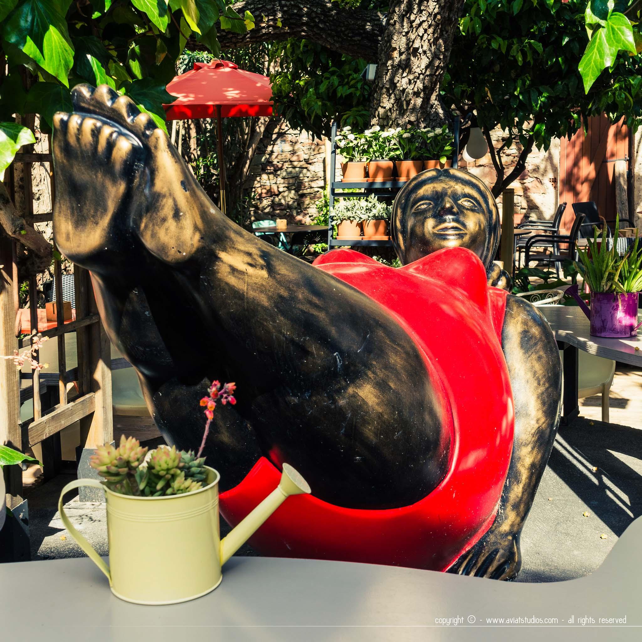 Sculpture d'une grosse dame en rouge dans le jardin de Mügs