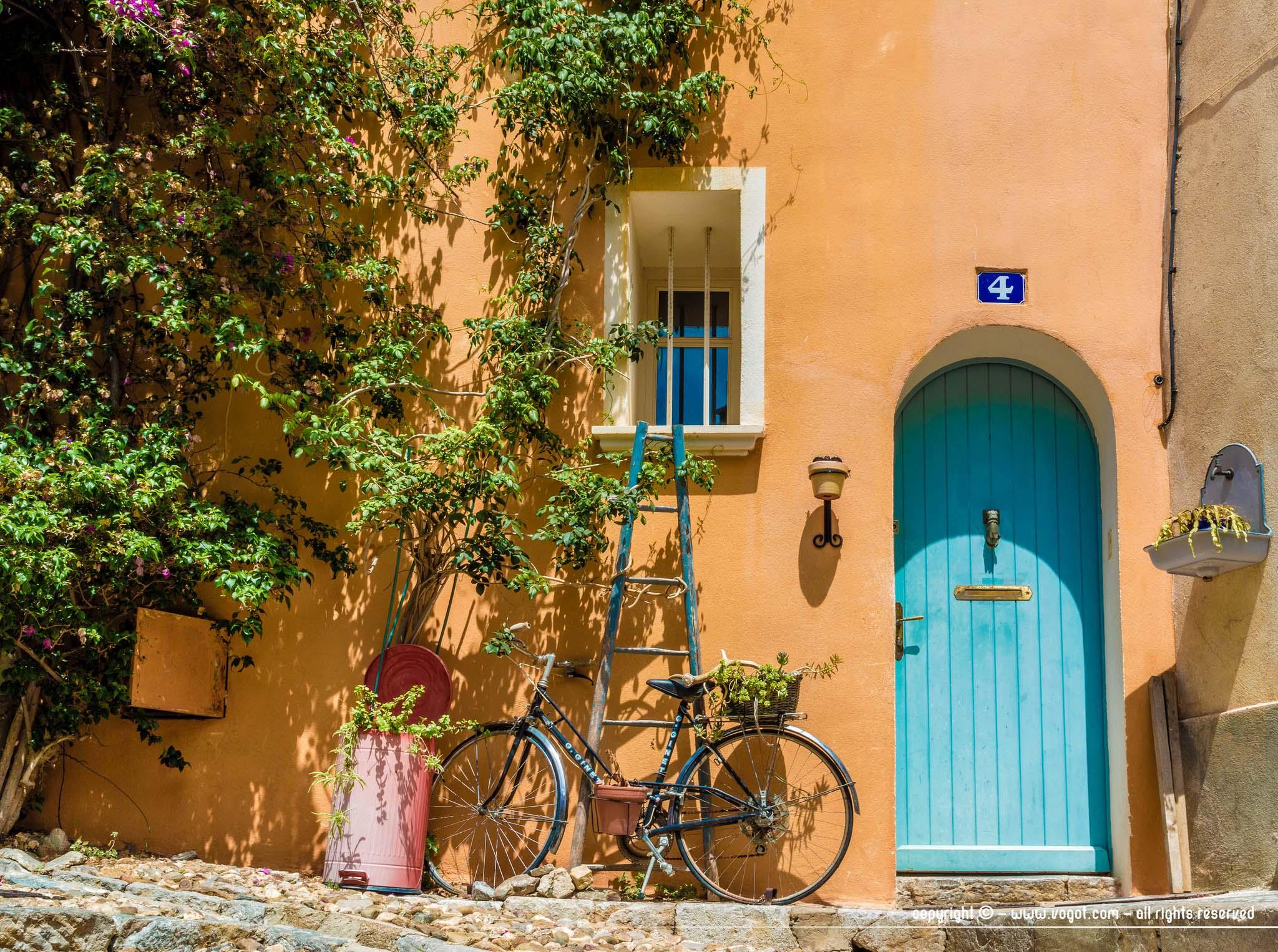 Une façade orangée baignée de soleil avec une porte bleue, un vélo, une échelle et de la végétation