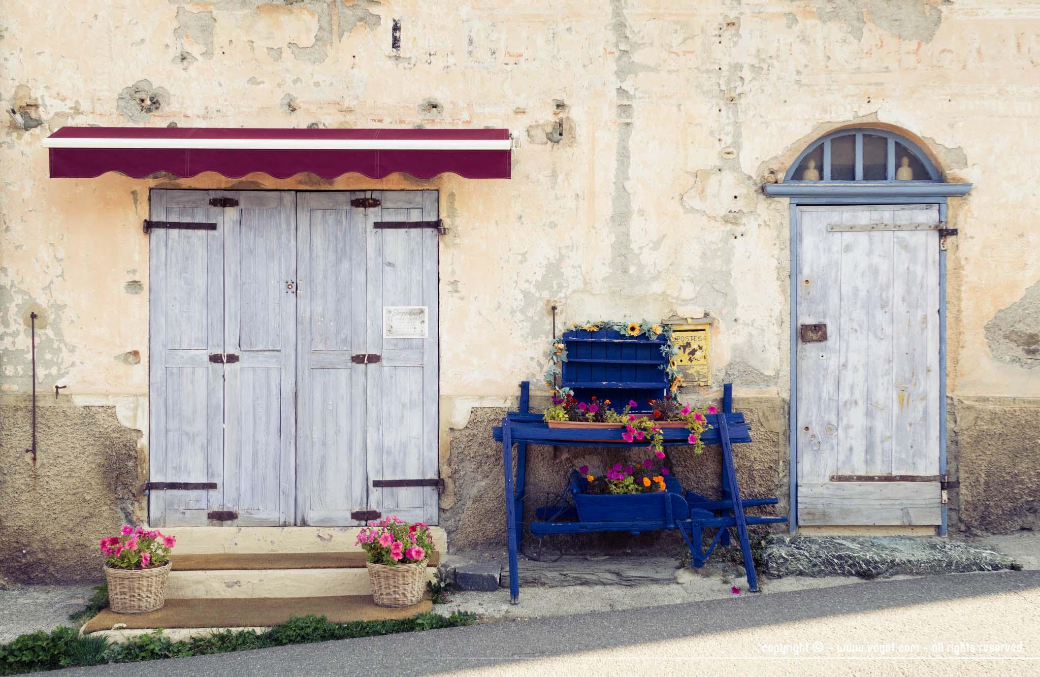 Saint-Véran - façade d'une boutique encore fermée avec des jardinières bleues