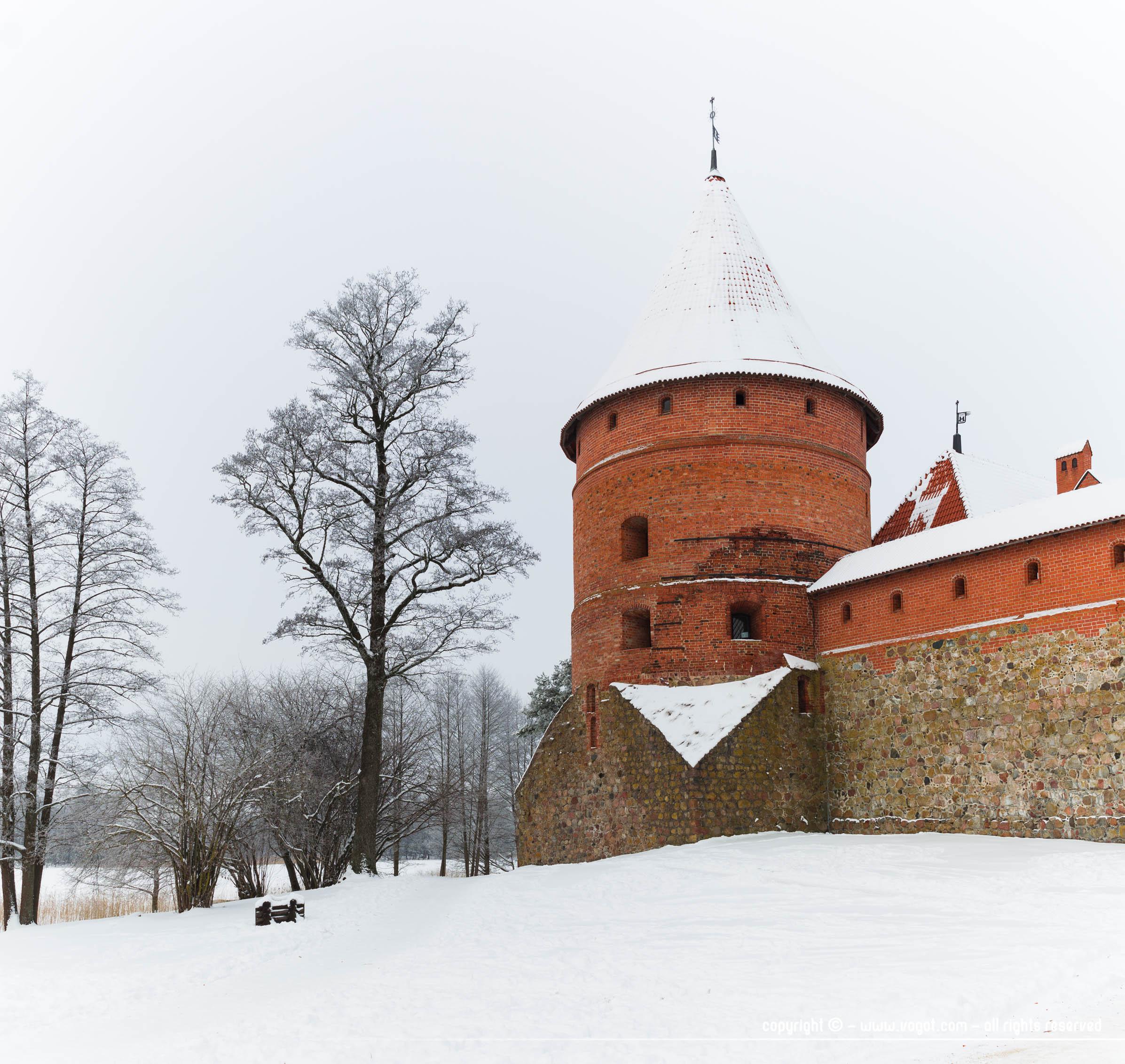Le château de Trakai en hiver - brique rouge sur fond blanc