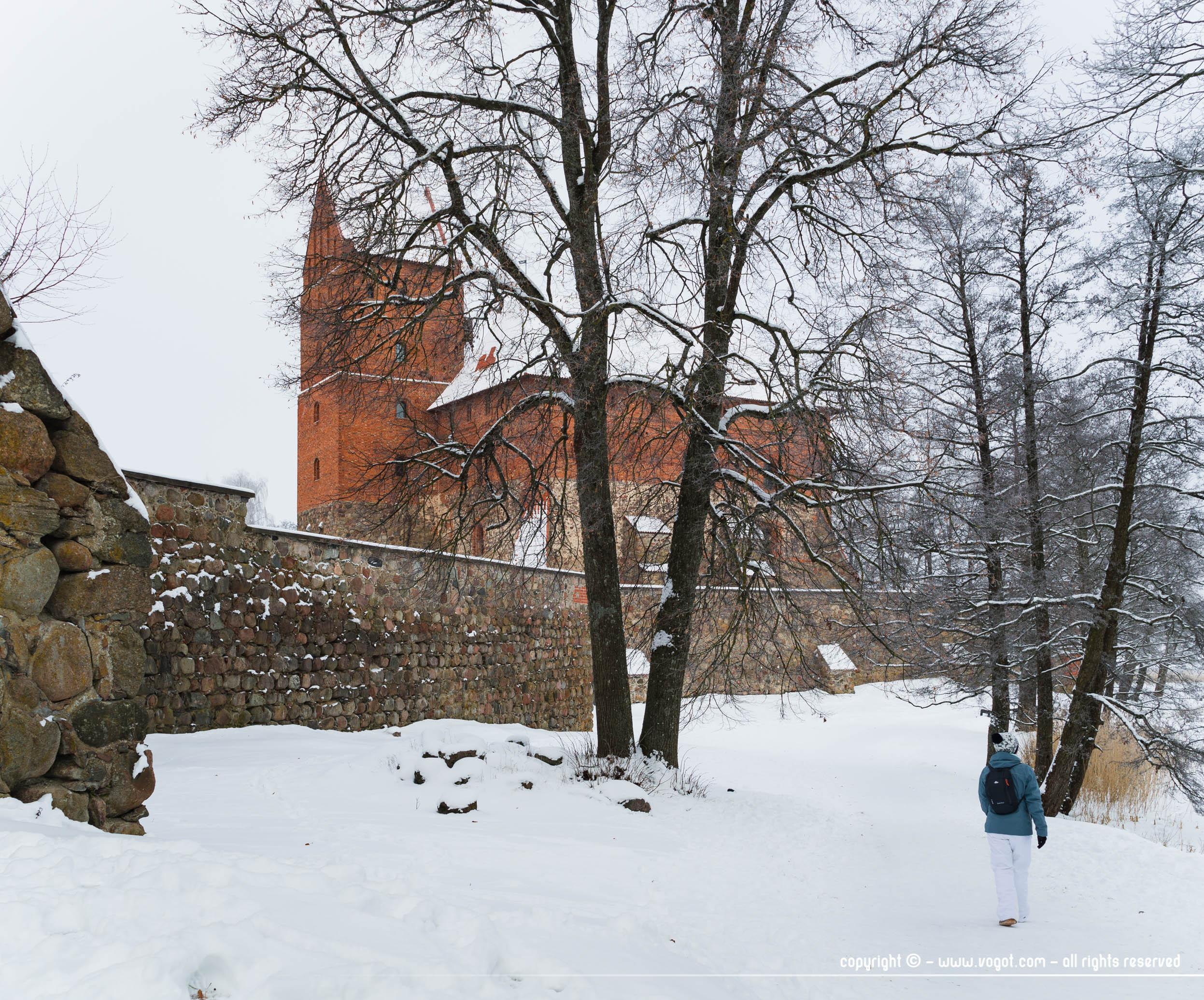 Chloé marchant le long des fortifications du château de Trakai en hiver donc sous la neige