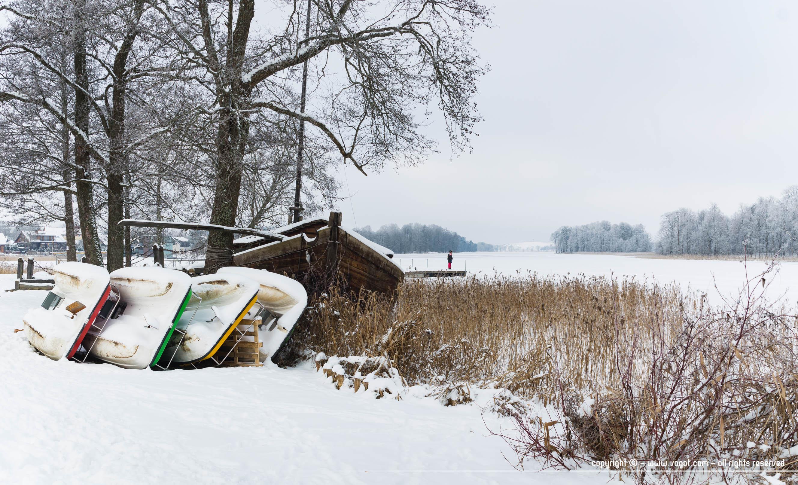 Petites embarcations recouvertes de neige le long d'un lac - Trakai