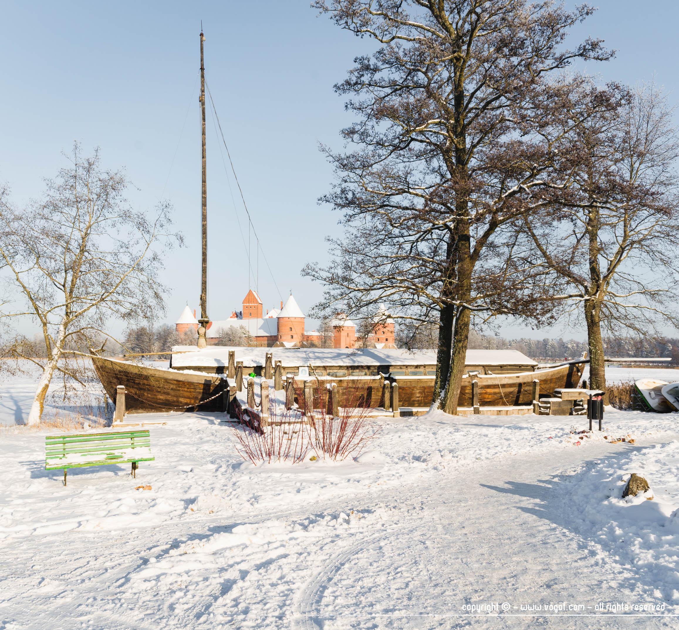 Bateau en bois sous la neige avec en arrière plan le château de Trakai