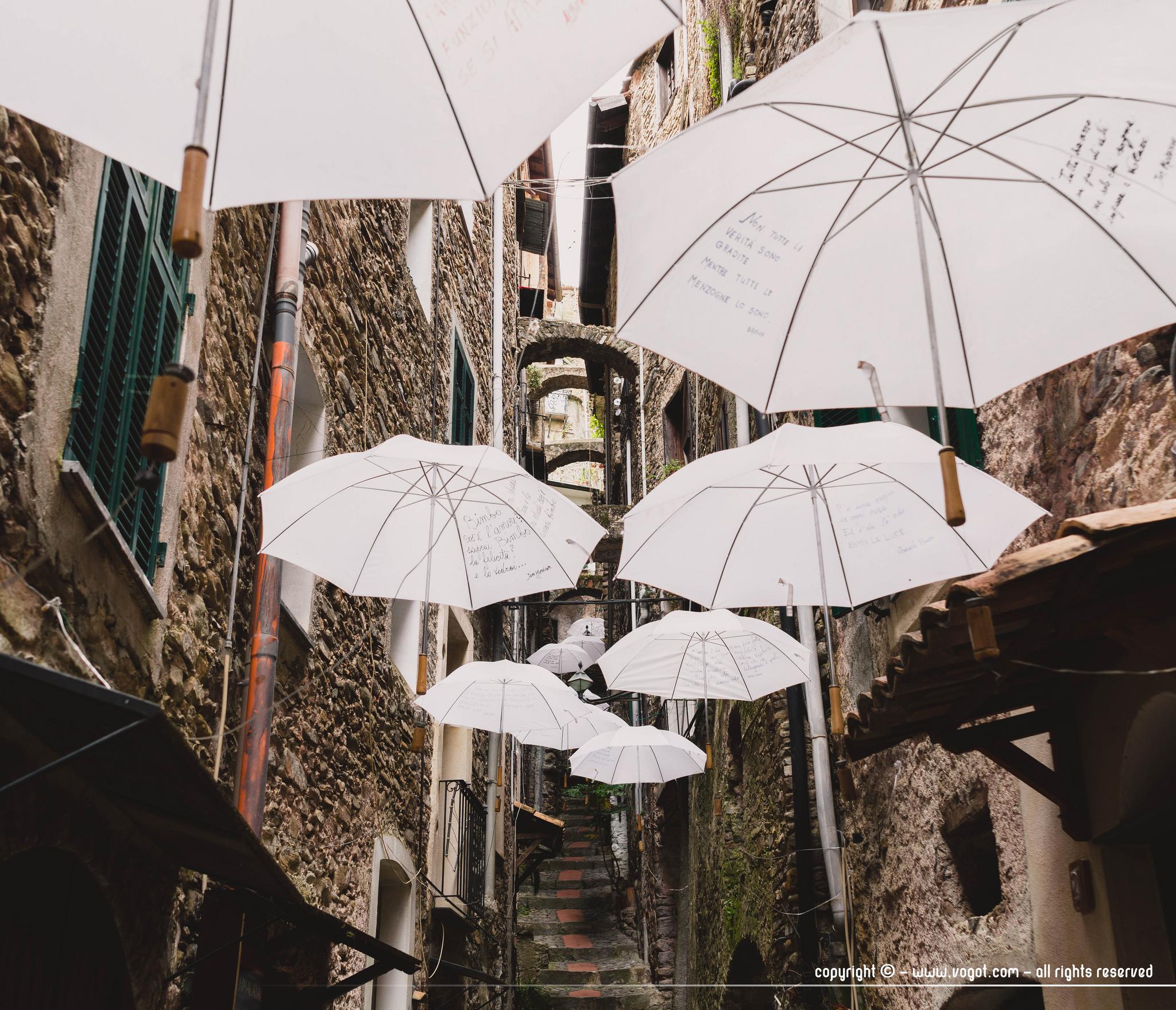 dolceacqua - des parapluies sont suspendues au-dessus d'une ruelle étroite